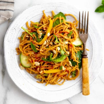 Overhead shot of cold Thai peanut noodle salad on a plate with a fork.
