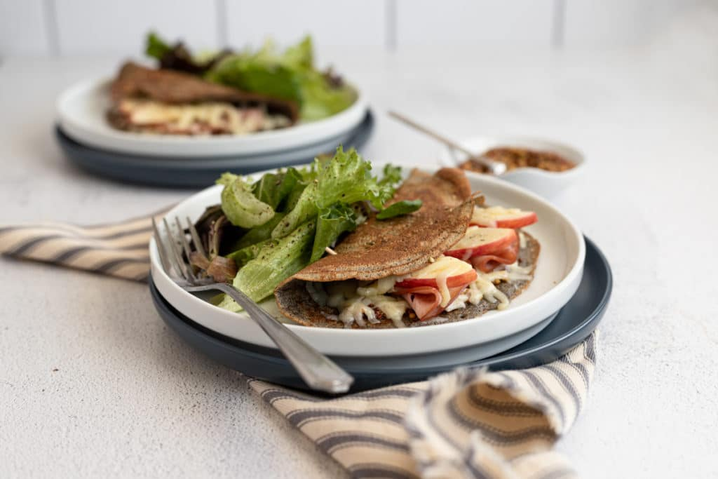 A buckwheat crepe on a plate filled with ham, cheese and apples, with a salad alongside.