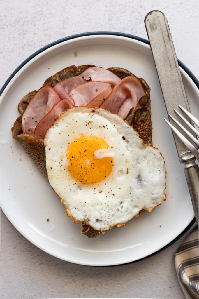 Close up of a crepe stuffed with sliced ham and topped with a fried egg.