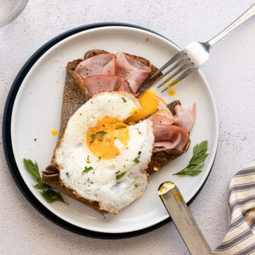 A buckwheat crepe on a plate topped with ham, cheese and a fried egg.