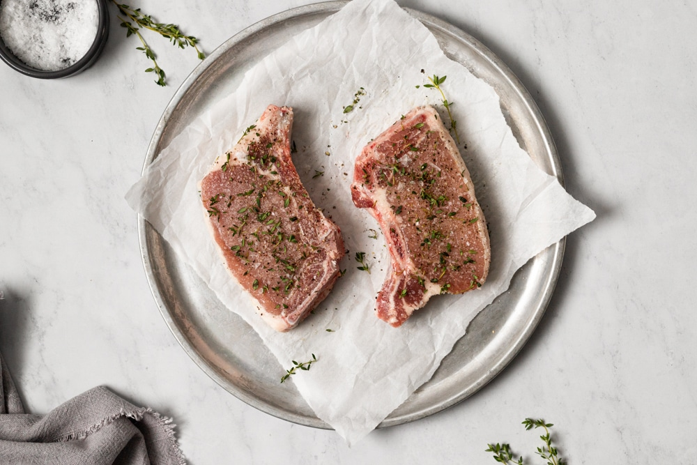 Two bone in pork chops on a plate, sprinkled with fresh thyme.