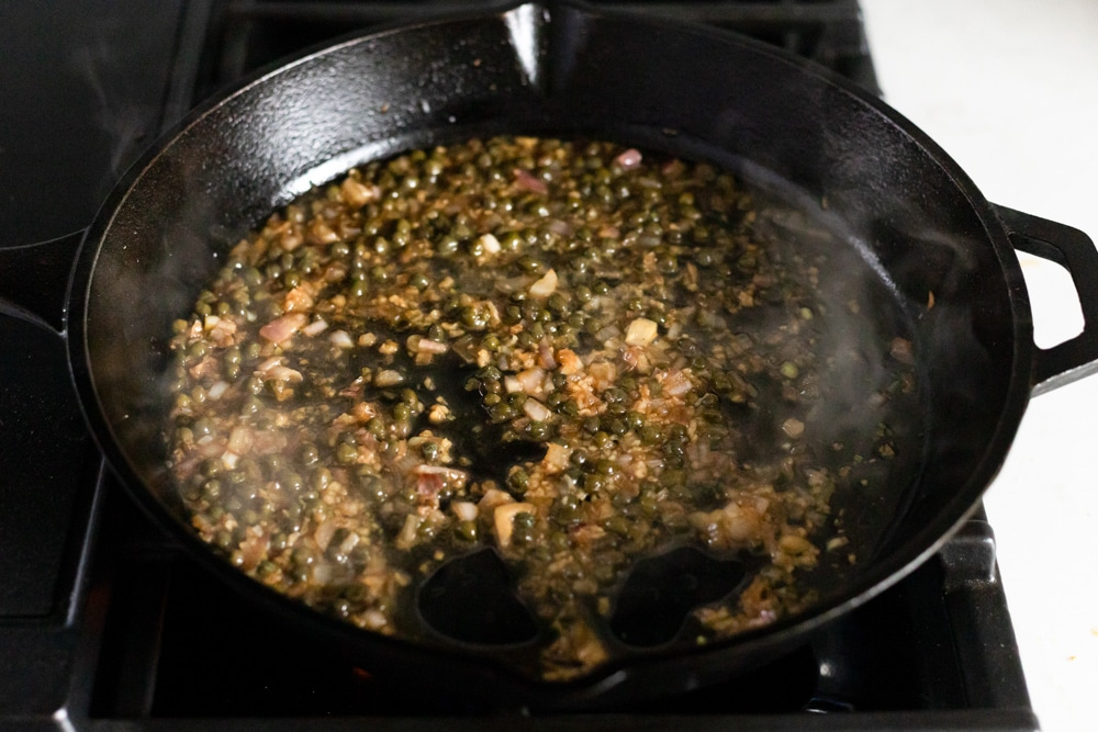 Process shot showing shallot caper sauce cooking in a cast iron skillet.