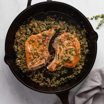 Pork chops in a cast iron skillet topped with pan sauce.
