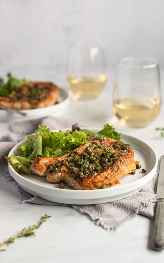 A cast iron pork chop on a plate, topped with shallot caper sauce, with a salad alongside.