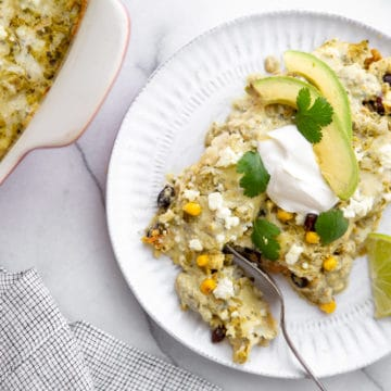 Salsa verde chicken enchiladas on a plate, topped with avocado and sour cream.