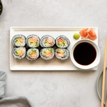 Homemade sushi on a plate with pickled ginger, tamari and chopsticks.