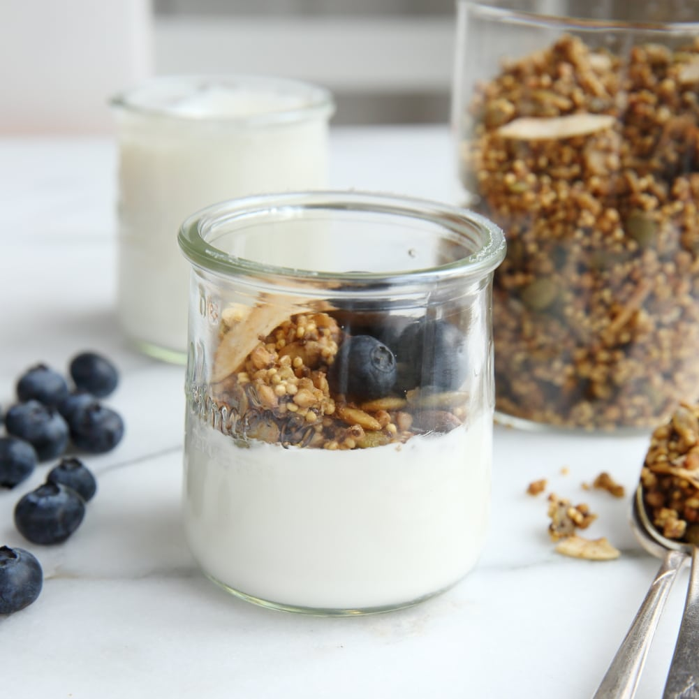 Millet granola in jar with yogurt and blueberries