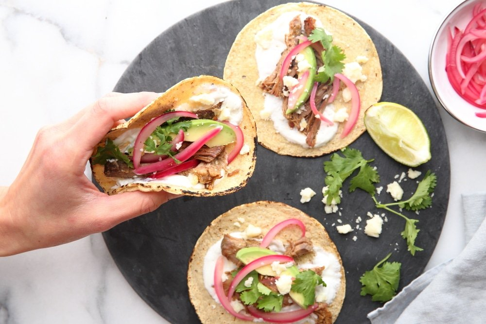 Hand holding a carnitas taco topped with pickled red onion and avocado.