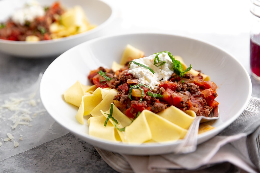 Lamb ragu with fresh mint and ricotta over papperdelle in bowl