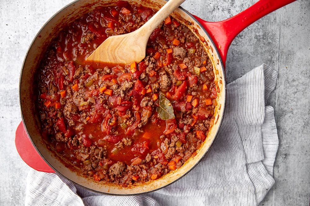 Lamb ragu in skillet with wooden spoon