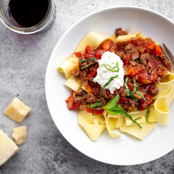 Lamb ragu with Papperdelle in bowl with cheese and wine on the side