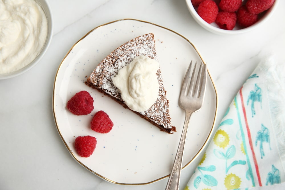 Chocolate cake on plate with whipped cream and raspberries