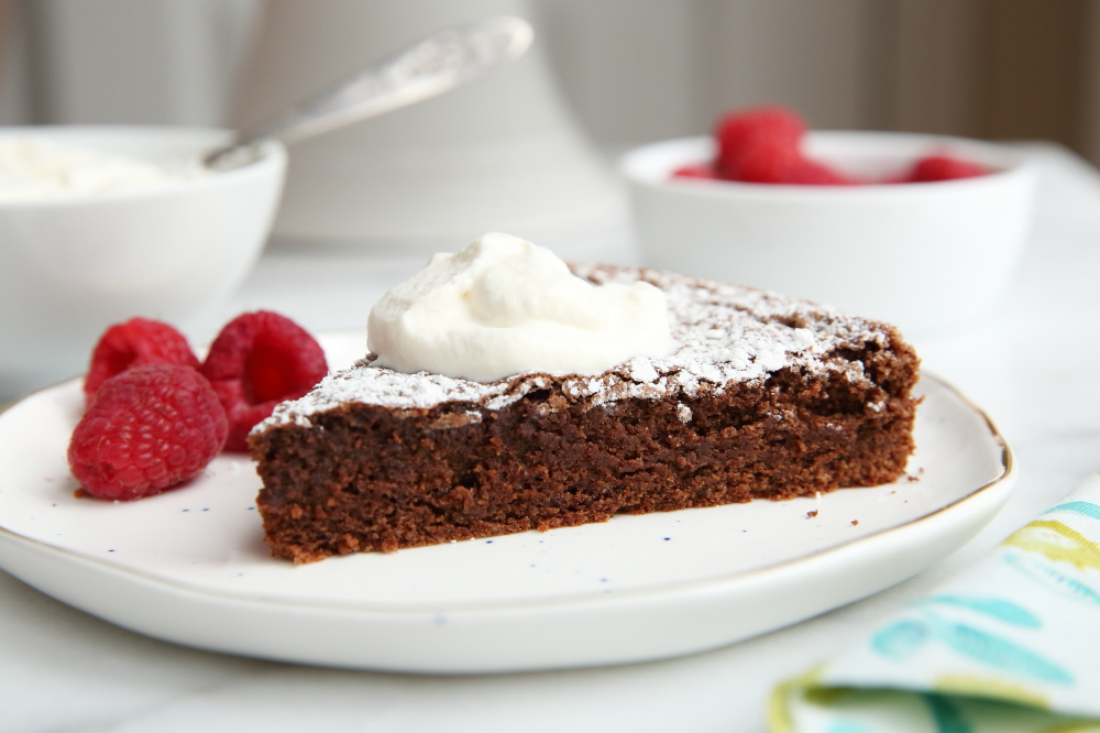gluten free chocolate almond cake on plate with whipped cream