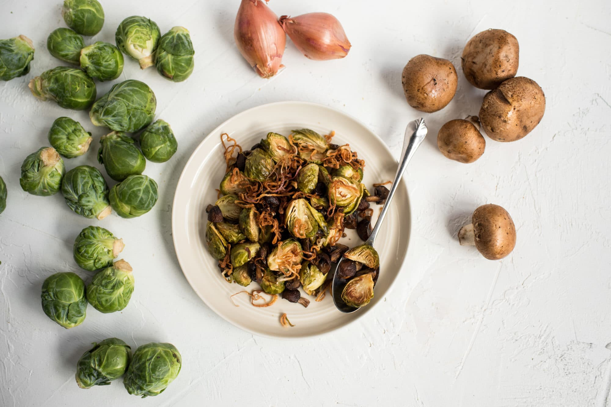 Caramelized Brussels Sprouts with Mushrooms and fried shallots on platter