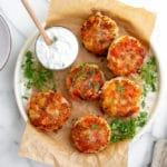 Salmon potato cakes on a platter with yogurt sauce alongside,