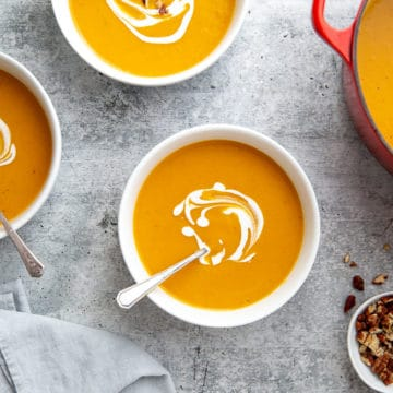 Overhead shot of bowls of healthy sweet potato soup on the countertop with a pot alongside.