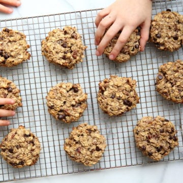 Banana oatcakes on cooling rack with hands grabbing them