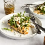 Grilled chicken paillard on a plate, topped with arugula salad.