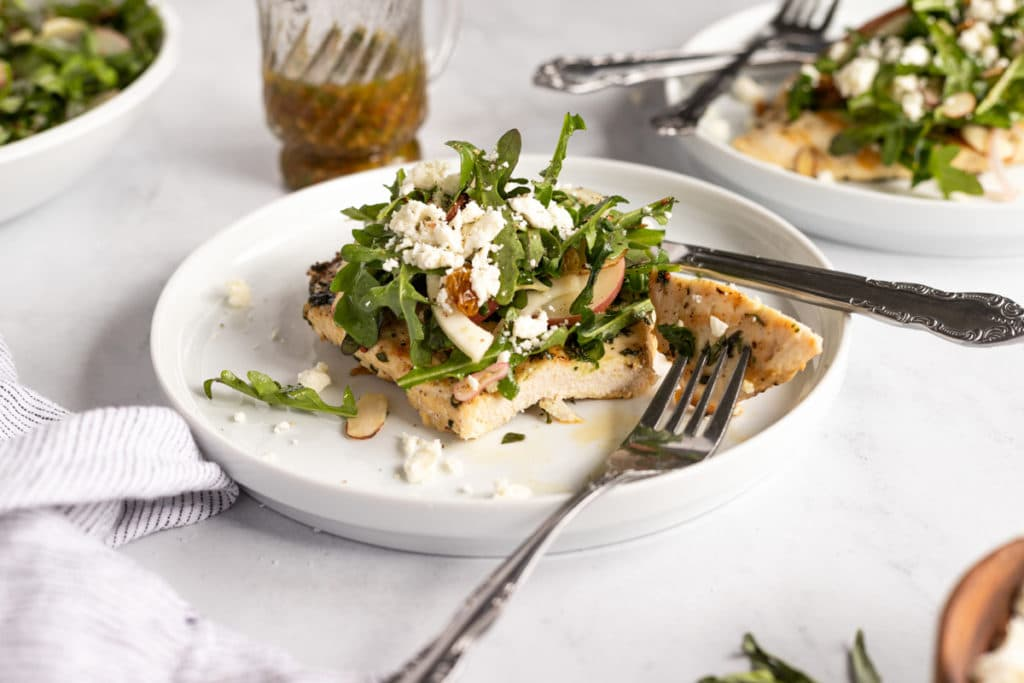 Chicken paillard on a plate with a fork and knife and a bite removed