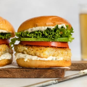 A fried fish sandwich topped with aioli, lettuce, tomato and avocado, on a serving board.