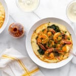 Coconut sriracha shrimp and kale in bowls over grits, with sriracha on the side