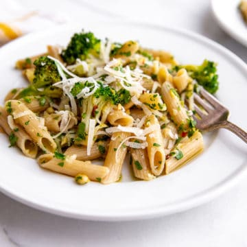 Broccoli pasta on plates with fork and napkin in the background