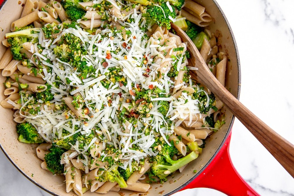 Broccoli pasta in pan with wooden spoon