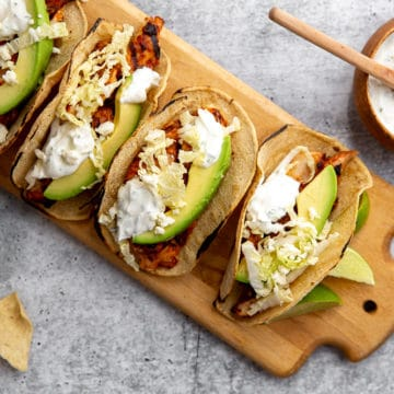 Easy chipotle chicken recipe served in tacos on a wooden cutting board with lime crema sauce on the side