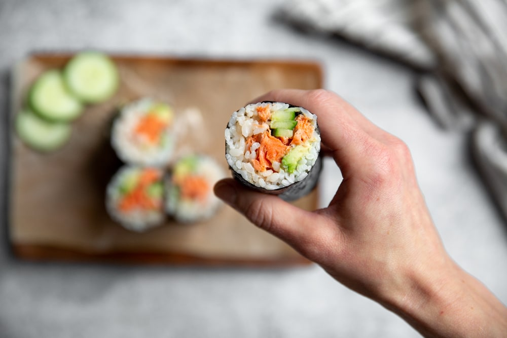 Hand holding a spicy salmon sushi burrito.