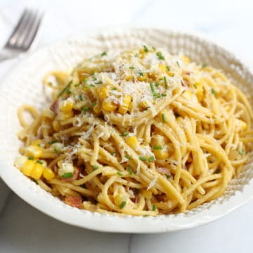 Pasta with corn and bacon in bowl with fork on the side