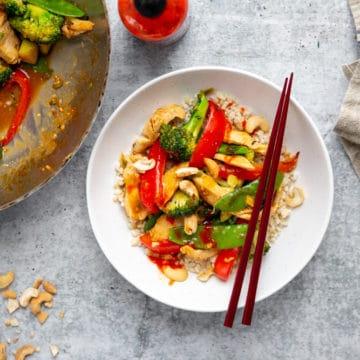 Healthy stir fry in a bowl with chopsticks, with a wok alongside.