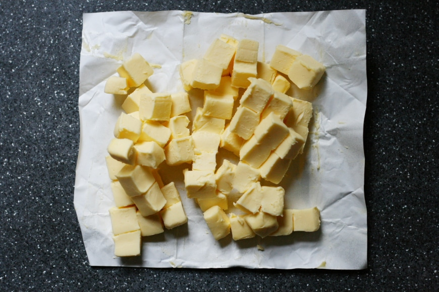 European butter cut into cubes on counter.