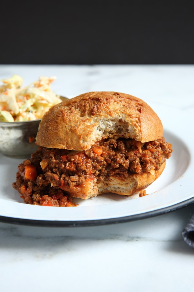 Healthy sloppy joes in bun on plate with coleslaw in the background