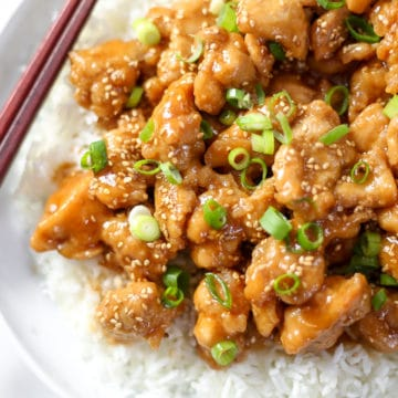 Overhead shot of gluten free sesame chicken over rice on a plate.