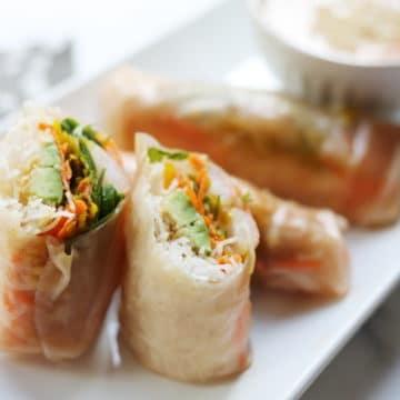 Side-view of shrimp winter rolls lined up on a serving platter.