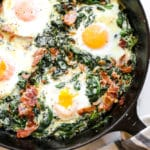 Spinach baked eggs in a cast iron skillet.