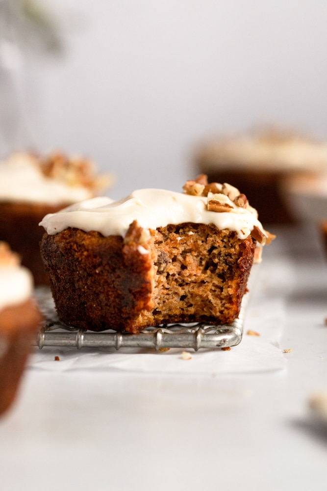 Close up of a gluten free carrot cake muffin with a bite taken out.