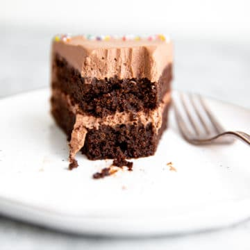 Close up of a slice of chocolate quinoa cake with chocolate whipped cream frosting, with a bite removed.