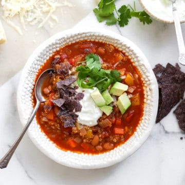 Overhead shot of a bowl of vegetable and quinoa chili on a table surrounded by toppings.