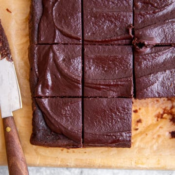 Black bean brownies on a cutting board with a knife.