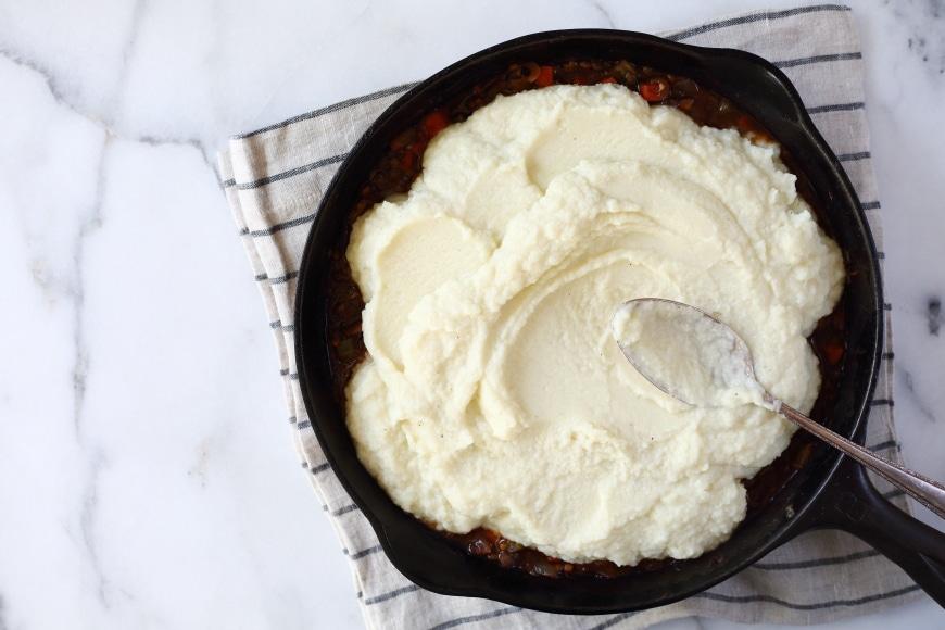 Uncooked lentil shepherds pie in cast iron skillet
