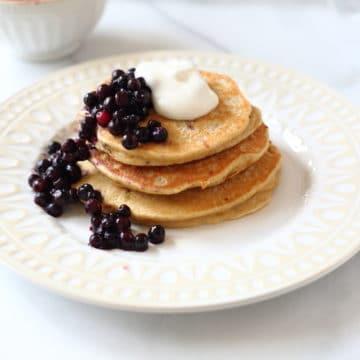 Banana Oat Blender pancakes on plate with berries and yogurt