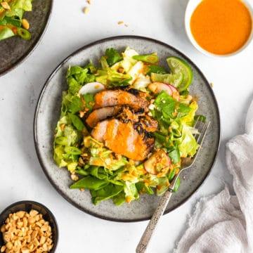 Gochujang pork tenderloin salad on a plate, with gochujang dressing alongside.