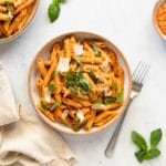Tomato pesto pasta in a bowl, topped with basil and shaved parmesan cheese.