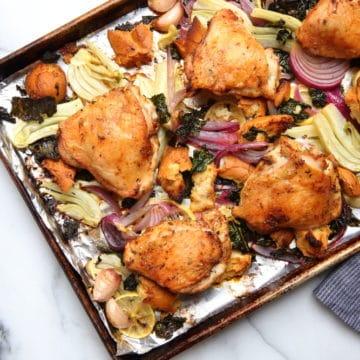 Sheet pan chicken thighs over winter panzanella salad.