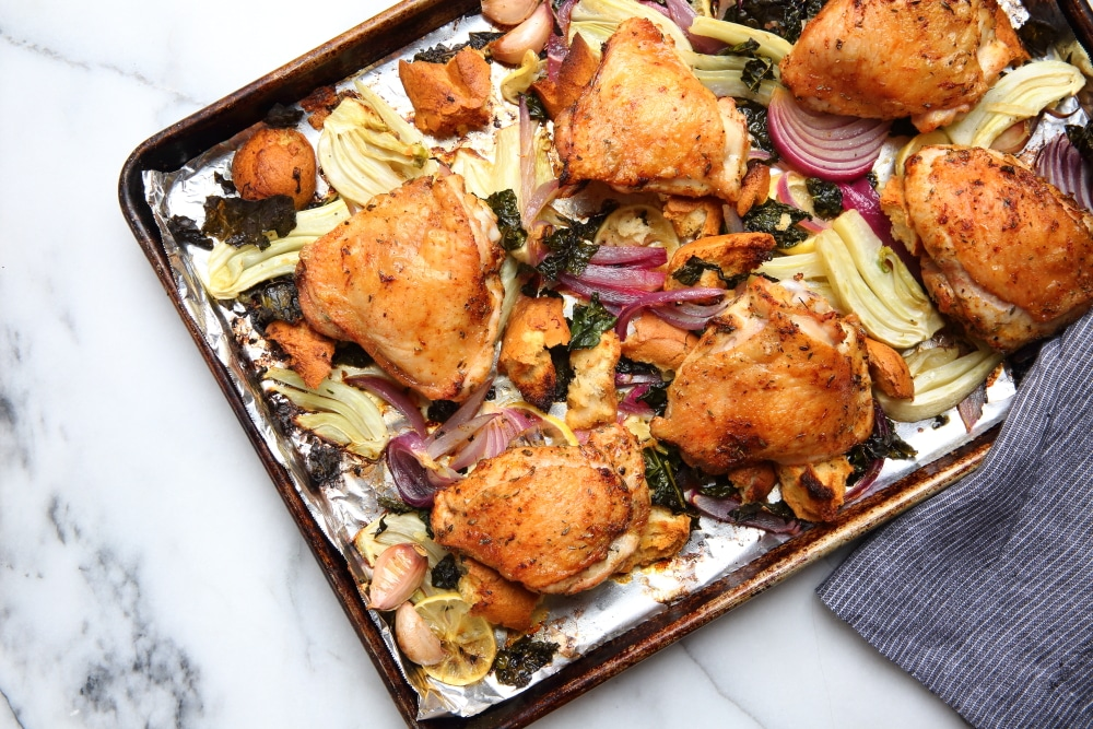 Sheet pan chicken thighs over panzanella salad
