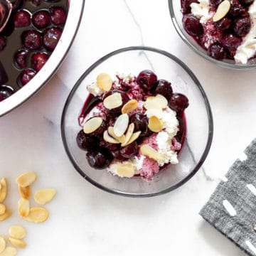 Cherries in port over sweet ricotta in serving glasses, with a pan of cherries to the side