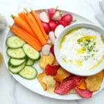 Yogurt feta dip in bowl with platter of vegetables and chips
