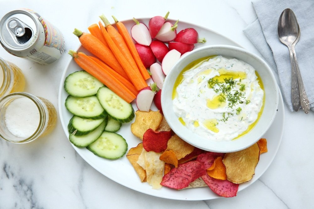 Yogurt dip in bowl with platter of veggies and chips for dipping