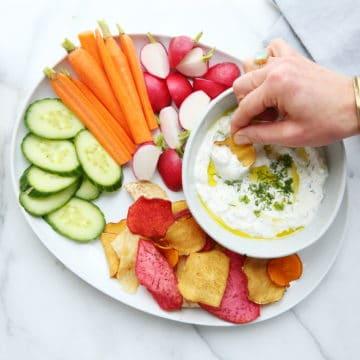 Yogurt feta dip in bowl with veggies and chips on platter